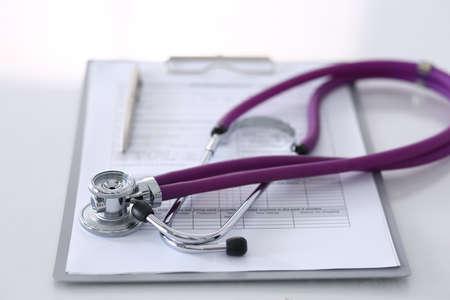 Formulario de registro de historial de medicación acostado sobre la mesa con estetoscopio y bolígrafo plateado. Concepto de medicina o farmacia. Herramientas médicas en la mesa de trabajo del médico Foto de archivo