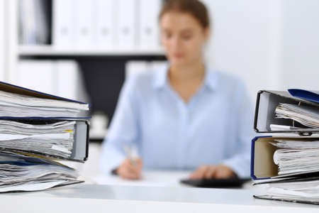 Binders with papers are waiting to be processed by business woman or bookkeeper back in blur. Internal Audit and tax concept Banco de Imagens
