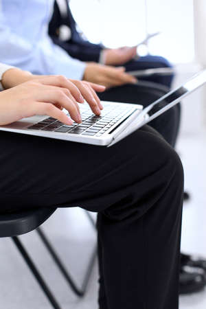 Group of business people sitting in office waiting for job interview, close-up. Hands of woman working on laptop. Conference or training concepts