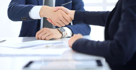 Group of business people or lawyers shaking hands finishing up a meeting , close-up. Success at negotiation and handshake concepts