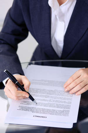 Unknown female hands with pen over document of contract. Agreement signing or business concept