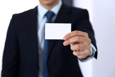 Unknown businessman hand holding business card with empty space, close-up