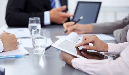 Woman hands using tablet at meeting. Business people group working together in office, close-up. Negotiation and communication concept