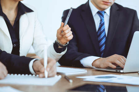 Group of business people at meeting, close up of woman hand raising for a quetion
