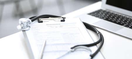 Stéthoscope, presse-papiers avec formulaire médical allongé sur la réception de l'hôpital avec ordinateur portable. Outils médicaux à la table de travail du médecin. Concept de médecine et de soins de santé