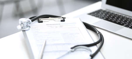Stetoscopio, appunti con modulo medico sdraiato sulla reception dell'ospedale con computer portatile. Strumenti medici al tavolo di lavoro del medico. Concetto di medicina e assistenza sanitaria