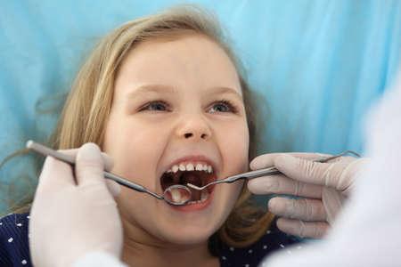 Kleines Baby, das während der mündlichen Untersuchung beim Arzt mit offenem Mund am Zahnarztstuhl sitzt. Zahnarztpraxis besuchen. Medizinkonzept