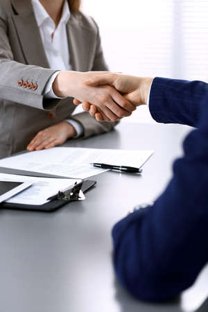 Business people shaking hands, finishing up a meeting. Papers signing, agreement and lawyer consulting concept.