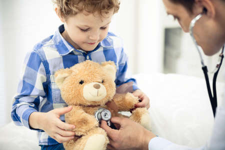 Doctor and patient child. Physician examining little boy. Regular medical visit in clinic. Medicine and health care concept
