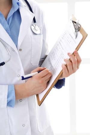 Medico femminile che utilizza modulo medico sul primo piano della lavagna per appunti. Il medico lavora in ospedale o in clinica. Concetto di assistenza sanitaria, assicurazione e medicina