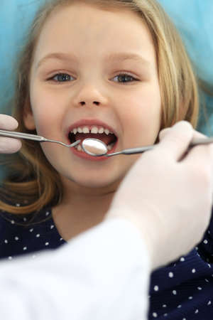 Little baby girl sitting at dental chair with open mouth during oral check up while doctor. Visiting dentist office. Medicine concept