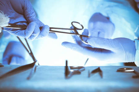 Surgeons hands holding surgical scissors and passing surgical equipment, close-up. Health care and veterinary concept Archivio Fotografico