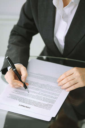 Business woman hands with pen over document of contract at glass table. Agreement signing concept
