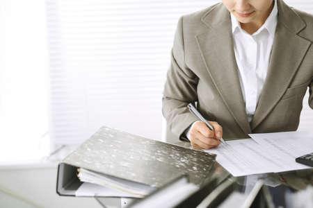 Boekhoudstervrouw of financiële inspecteur die rapport maakt, saldo berekent of controleert, close-up. Bedrijfs-, audit- of belastingconcepten Stockfoto