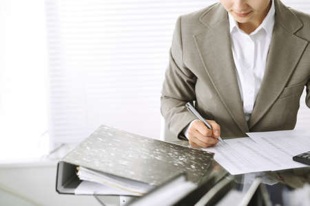 Bookkeeper woman or financial inspector  making report, calculating or checking balance, close-up.  Business, audit or tax concepts 免版税图像