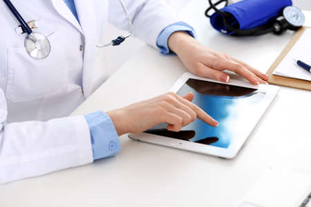 Doctor working table. Woman physician using tablet computer while sitting in hospital office close-up. Healthcare, insurance and medicine concept Stock Photo