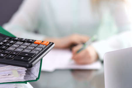 Bookkeeper or financial inspector  making report, calculating or checking balance. Audit and tax service concept. Green colored image background