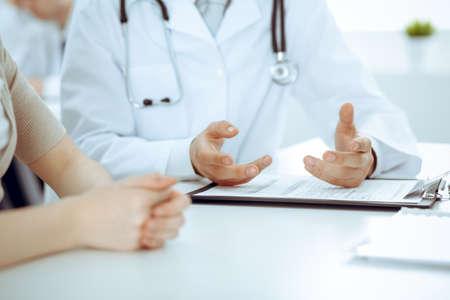 Lekarz i pacjent dyskutują o czymś, tylko ręce przy stole. Koncepcje medycyny i opieki zdrowotnej