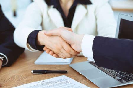 Geschäftsleute, die sich bei Treffen oder Verhandlungen im Büro die Hände schütteln. Handshake-Konzept. Partner sind zufrieden, weil Vertragsunterzeichnung