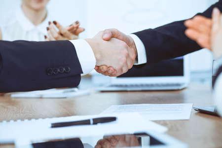 Geschäftsleute, die sich bei Treffen oder Verhandlungen im Büro die Hände schütteln. Handshake-Konzept. Partner sind zufrieden, weil Vertragsunterzeichnung Standard-Bild