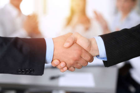 Business people shaking hands at meeting while theirs colleagues clapping and applauding. Group of unknown businessmen and women in modern white office. Success teamwork, partnership and handshake concept Imagens - 121621101