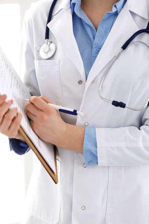 Femme médecin à l'aide d'un formulaire médical sur le presse-papiers agrandi. Le médecin travaille à l'hôpital ou à la clinique. Concept de soins de santé, d'assurance et de médecine