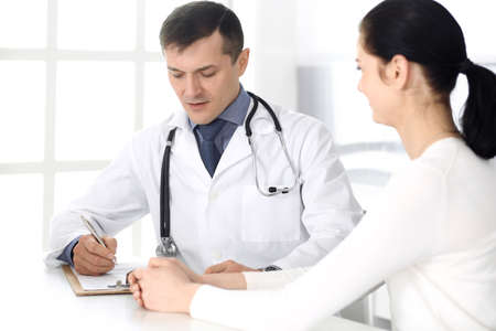 Doctor and patient discussing medical exam resoults at hospital office. Physician using clipboard for filling up medication history records. Perfect medical service in clinic. Medicine and healthcare concepts Stockfoto - 121111489