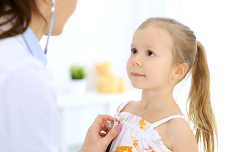 Doctor examining a little girl by stethoscope. Happy smiling child patient at usual medical inspection. Medicine and healthcare concepts Stockfoto - 121111493