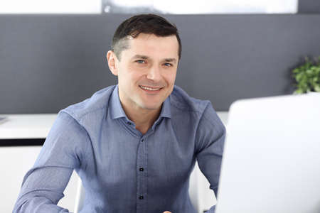 Cheerful smiling businessman working with computer in modern office. Headshot of male entrepreneur or director of a company at the workplace. Business concept