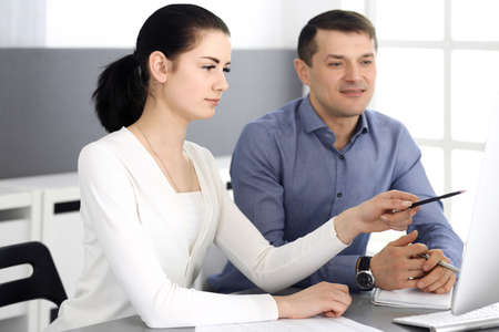 Cheerful smiling businessman and woman working with computer in modern office. Headshot at meeting or workplace. Teamwork, partnership and business concept Stockfoto - 121111499