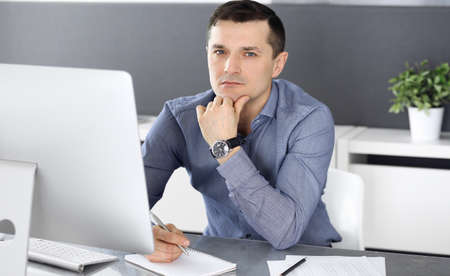 Businessman working with computer in modern office. Headshot of male entrepreneur or company director at workplace. Business concept Stockfoto - 121111500