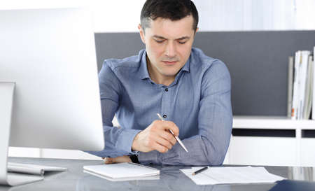 Businessman working with computer in modern office. Headshot of male entrepreneur or company director at workplace. Business concept Stockfoto