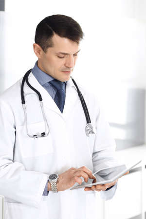 Doctor man using tablet computer for network research or virtual disease treatment. Perfect medical service in clinic. Happy future for modern  medicine, medic data and healthcare concepts