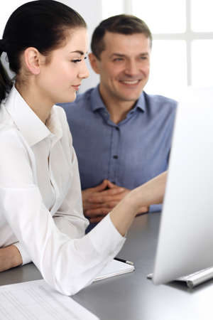 Cheerful smiling businessman and woman working with computer in modern office. Headshot at meeting or workplace. Teamwork, partnership and business concept