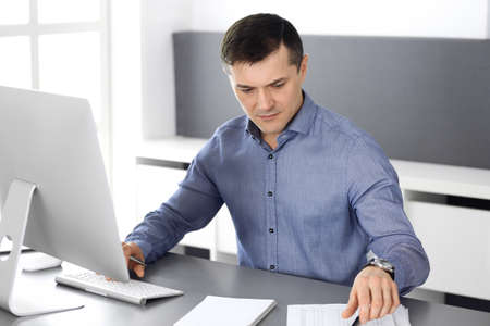 Businessman working with computer in modern office. Headshot of male entrepreneur or company director at workplace. Business concept Stockfoto - 121111560