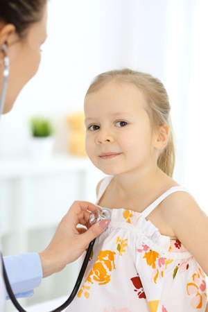 Doctor examining a little girl by stethoscope. Happy smiling child patient at usual medical inspection. Medicine and healthcare concepts Stockfoto - 121111569