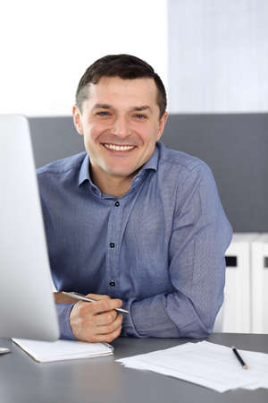 Cheerful smiling businessman working with computer in modern office. Headshot of male entrepreneur or director of a company at the workplace. Business concept Stockfoto - 121111689