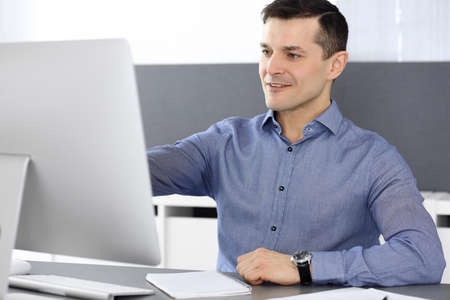 Cheerful smiling businessman working with computer in modern office. Headshot of male entrepreneur or director of a company at the workplace. Business concept Stockfoto - 121111710