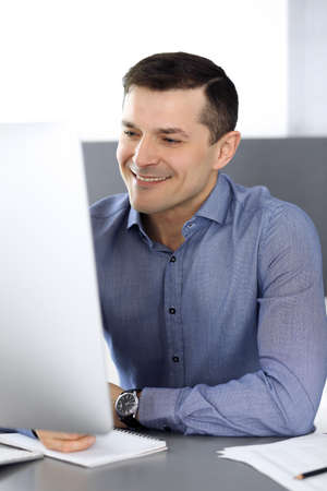 Cheerful smiling businessman working with computer in modern office. Headshot of male entrepreneur or director of a company at the workplace. Business concept Stockfoto - 121111731