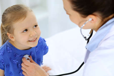 Doctor examining a little girl by stethoscope. Happy smiling child patient at usual medical inspection. Medicine and healthcare concepts Stockfoto - 121111734