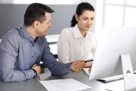 Cheerful smiling businessman and woman working with computer in modern office. Headshot at meeting or workplace. Teamwork, partnership and business concept Stockfoto - 121111736
