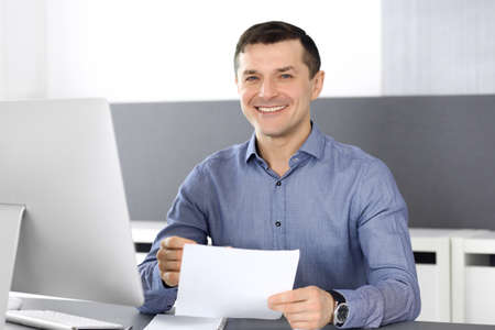 Cheerful smiling businessman working with computer in modern office. Headshot of male entrepreneur or director of a company at the workplace. Business concept Stockfoto - 121111740