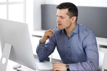 Businessman working with computer in modern office. Headshot of male entrepreneur or company director at workplace. Business concept Stockfoto - 121111741