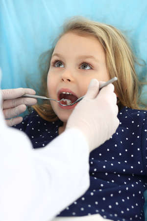 Little baby girl sitting at dental chair with open mouth during oral check up while doctor. Visiting dentist office. Medicine concept Stockfoto - 121111882