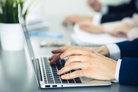 사무실에서 함께 일하는 비즈니스 사람들의 그룹입니다. 노트북 컴퓨터에 입력하는 남자 손