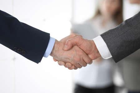 Geschäftsleute, die sich bei Treffen oder Verhandlungen die Hände schütteln, Nahaufnahme. Gruppe unbekannter Geschäftsleute und Frauen im modernen Büro im Hintergrund. Teamwork, Partnerschaft und Handschlagkonzept