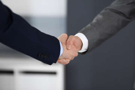 Business people shaking hands at meeting or negotiation in modern office, close-up. Teamwork, partnership and handshake concept Imagens