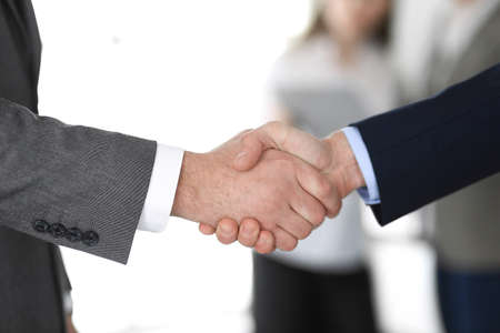 Business people shaking hands at meeting or negotiation, close-up. Group of unknown businessmen and women in modern office at background. Teamwork, partnership and handshake concept Imagens - 121351124