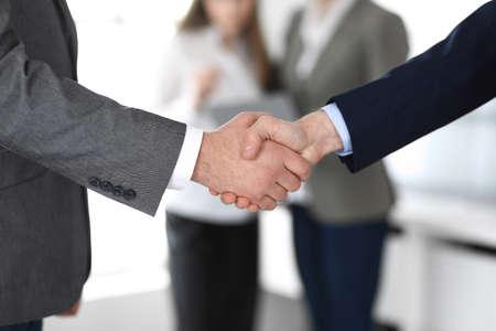Les gens d'affaires se serrant la main lors d'une réunion ou d'une négociation, en gros plan. Groupe d'hommes et de femmes inconnus dans un bureau moderne à l'arrière-plan. Concept de travail d'équipe, de partenariat et de poignée de main