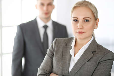 Business woman standing straight with colleague businessman in office, headshot. Success and corporate partnership concept
